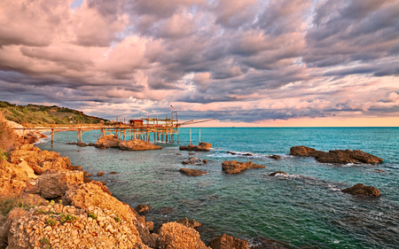 Rocca San Giovanni, Chieti, Abruzzo, Italië: landschap van de Adriatische kust bij zonsopgang met een typische mediterrane vissershut trabocco, onder een dramatische bewolkte hemel Stockfoto