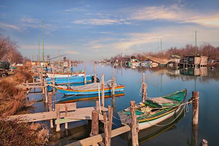 Ravenna, Emilia Romagna, Italien: Landschaft des Feuchtgebiets im Naturschutzgebiet Po Delta Park mit kleinen Booten und Fischerhütten im Fluss Standard-Bild