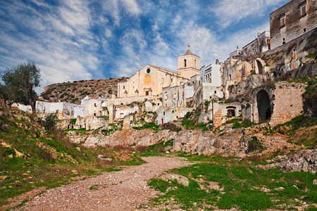Ginosa, Taranto, Puglia, Italy: landscape of the old village partly abandoned with the ancient church and the cave houses carved into the tufa rock Stock Photo