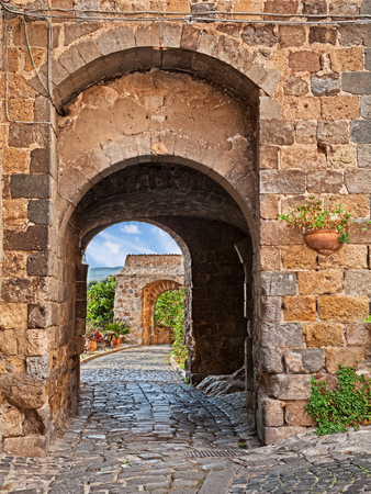Bolsena, Viterbo, Lazio, Italy: ancient city gate and cobbled alley in the old town