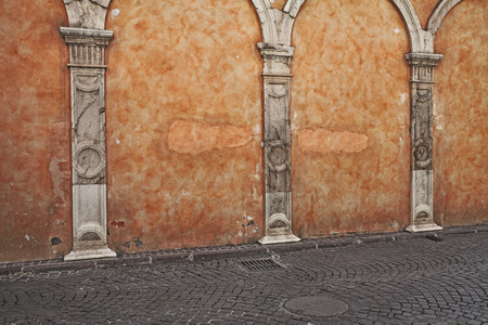 An old wall with scratched stained plaster, ancient stone columns and porphyry sidewalk - orange pastel grunge urban background