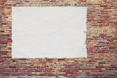 blank advertising poster glued to the brick wall - copy space in street billboard  Stock Photo