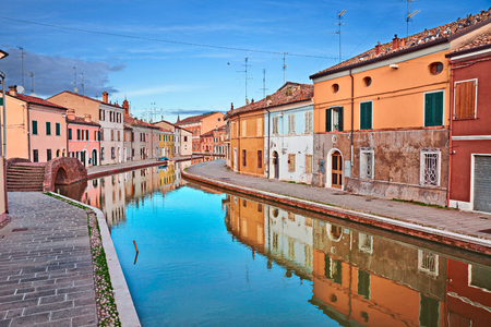 Comacchio, Ferrara, Emilia Romagna, Italy: view of the colored houses with mirror on the water of the canal in the old town known as the Little Venice Stock Photo