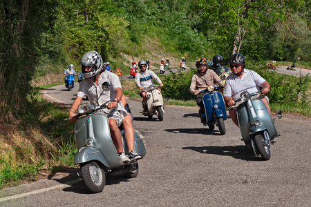 group of bikers riding vintage italian scooters Vespa and Lambretta on the hills during the scooter rally I colli di Romagna in Cesena, FC, Italy - June 26, 2016