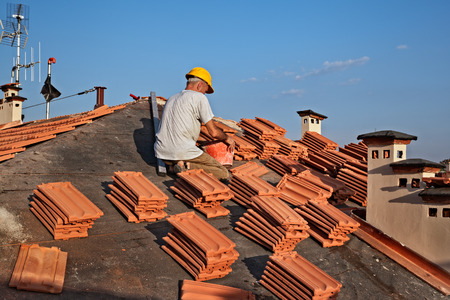 construction worker on a roof covering it with tiles - roof renovation, roofing installation of tar paper, new tiles and chimney Stock Photo