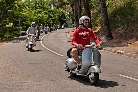 group of bikers riding vintage italian scooters Vespa and Lambretta on the italian countryside during the motorcycle rally Vespagiro on May 25, 2014 in Montiano, FC, Italy