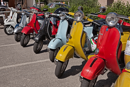row of vintage italian scooters Vespa and Lambretta parked during the classic motorcycle rally Vespagiro on May 25, 2014 in Montiano, FC, Italy