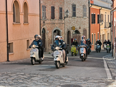 group of bikers riding vintage Italian scooters Vespa and Lambretta in motorcycle rally of Vespa Club Santarcangelo on April 9, 2012 in Verucchio, RN, Italy