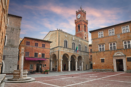 Pienza, Siena, Tuscany, Italy: the main square with the ancient city hall and the beautiful water well of the picturesque medieval town