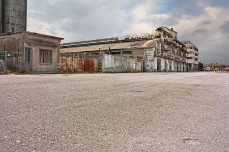 wide street in the suburbs of the city with abandoned warehouse and factory - desolate landscape in the outskirts of the town with empty road and ruined factories