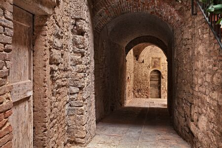 Todi, Umbria, Italy: ancient narrow alley with underpass in the medieval Italian town - picturesque dark city corner