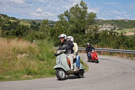 Couple riding vintage scooter Vespa in the italian hills during the rally Raduno Vespa e Lambretta, on June 21, 2015 in Forlimpopoli, FC, Emilia-Romagna, Italy Editorial