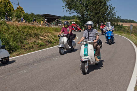 Group of bikers riding vintage italian scooters Lambretta and Vespa on the hills during the scooter rally I colli di Romagna, on June 26, 2016 in Cesena, FC, Italy