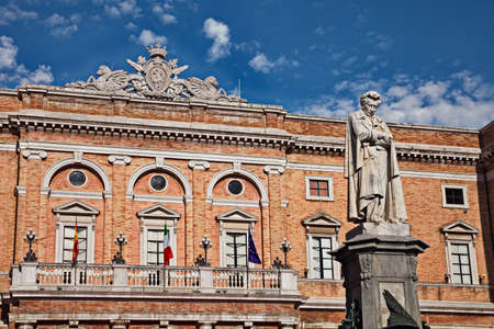 Recanati, Marche, Italy: the main square with the statue of the poet Giacomo Leopardi and the city hall in neoclassical style