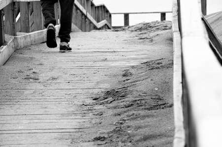 lonely boy: a lonely boy walking on a wooden bridge near the sea
