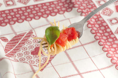 herba: Spaghetti with fresh tomato rolled on fork. Traditional Italian Food Stock Photo