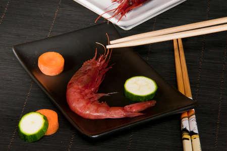 fished: red fresh shrimp served on a rectangular plate with black chopsticks Japanese