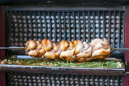 pollo rostizado: pollo asado y patatas cerca de la entrada de un local en Par�s Foto de archivo