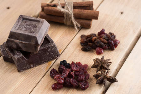 sweet segments: pieces of chocolate on wooden table. Chocolate, spices and dried fruit antidepressants