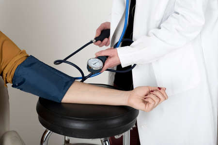 measures: Doctor measures the blood pressure of a patient woman.