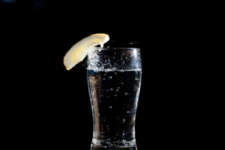 thirst quenching: fresh slice of lemon falling in water, black background