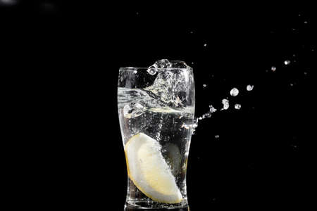 thirst quenching: fresh slice of lemon falling in water Stock Photo