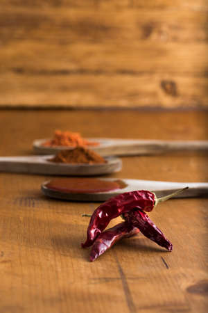 red chili pepper , some whole, some ground, some chopped and some homemade sauce on wooden table