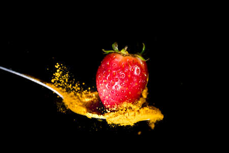 Splash of turmeric, caused by a fall of a strawberry on a spoon on a black background. Stock Photo