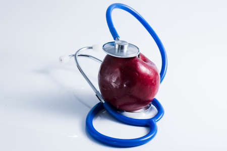Red apple with stethoscope on table