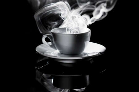 small white cup of steaming coffee on a black background Standard-Bild - 134727959