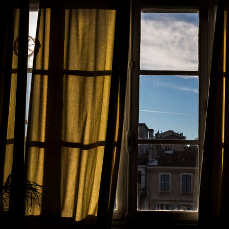 inside of a blind window with curtain, you see a glimpse of Marseille Imagens