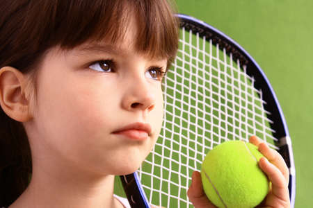 Portrait of a young girl with a tennis racket. photo
