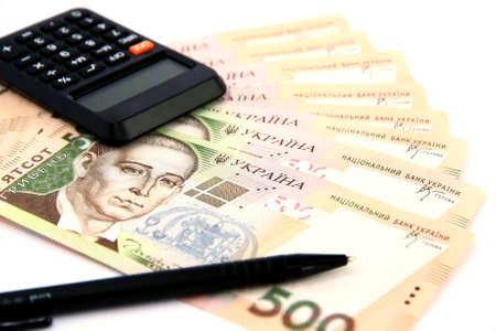 Ukrainian hryvnia, calculator and pen on a white  photo