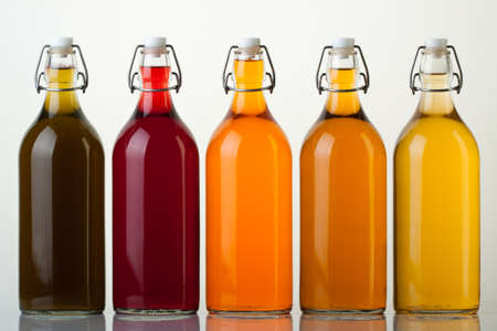 Five glass bottles with colored liquid on white background