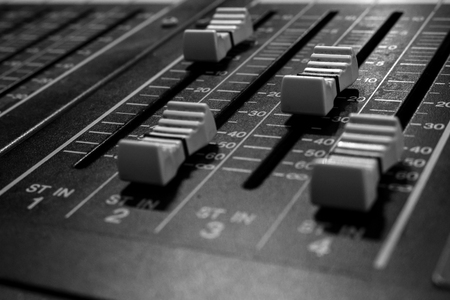 Closeup view of Faders on Professional digital Audio mixing control Console with zero decimal indicators