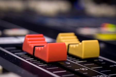Red and Yellow Professional Audio Mixing Console Faders, selective focus