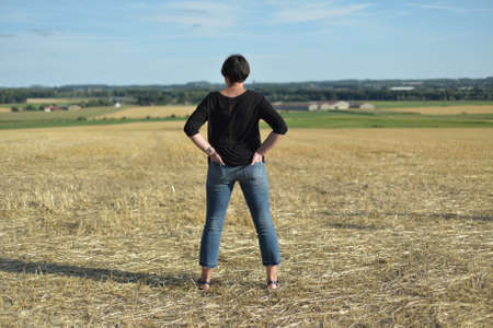 A woman looks at a mown field Stock Photo