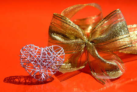 White heart made of wire with golden bow on red background.