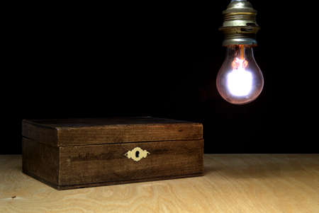 Old wooden casket on a table against a lightbulb against a black background.