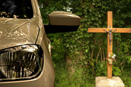 Parking car with crucifix in the background. Drive carefully!