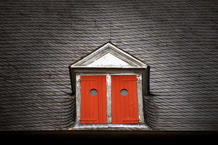 Dormer with red shutters on a slate roof