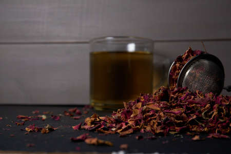 Round infuser on pile of tea of dried rose petals with cup in the background on wooden table