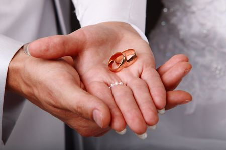 Image of a young couple holding wedding rings on hands photo