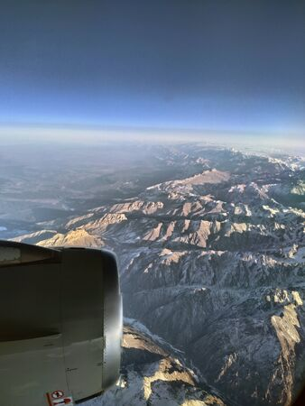 A jet engine is seen through the plane's window while flying over mountains