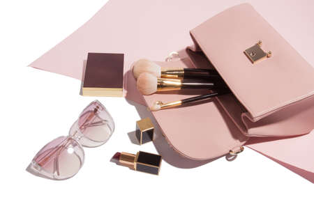 Layout of female coral pink leather handbag stuff of make up brushes