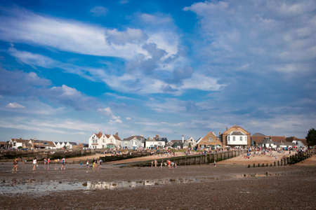 WHITSTABLE, UK - AUGUST 21 2014: People are looking for crabs and clams on the sea bed at low tide in Whitstable. Visitors to can also be seen on the dock side. The harbour was built by the Canterbury and Whitstable Railway Company in 1832. Redakční