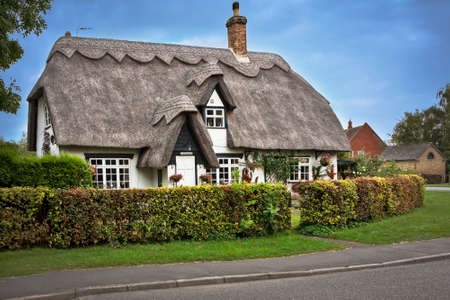 english countryside: COTSWOLDS, UK - OCTOBER 12, 2014: Charming thatched roof house in the Cotswolds English countryside.