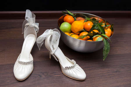 deep orange: Luxury ivory wedding accessories for bride and Bright deep orange Clementine or Mandarins  in a bowl