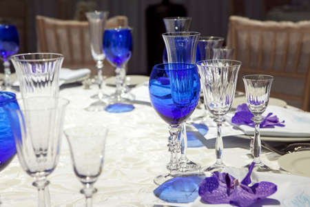 servilleta de papel: serviette on a plate served on the festive table. Blue goblet and violet orchid