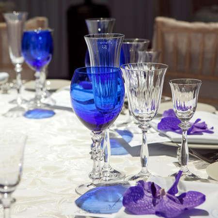 servilleta de papel: servilleta en un plato servido en la mesa festiva. cubilete azul y violeta orquídea Foto de archivo